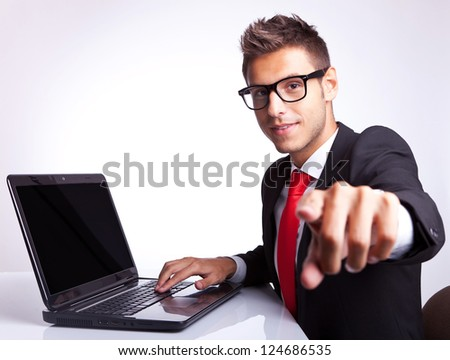 side view of a business man pointing his finger to the camera while working at laptop computer