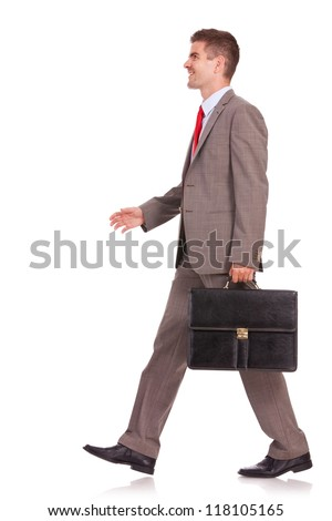 side view of a business man with briefcase walking and smiling, isolated on white - stock photo