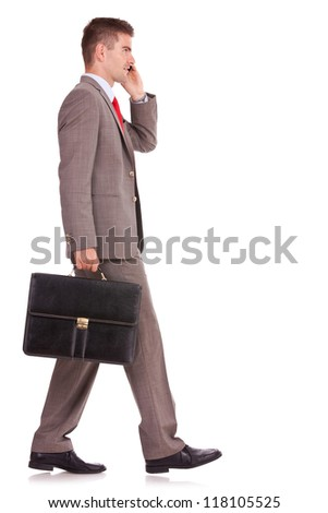 side view of a business man with his briefcase, talking on the mobile phone on white background - stock photo