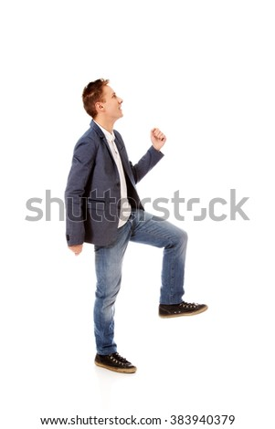 Side view of a businessman climbs the stairs - stock photo