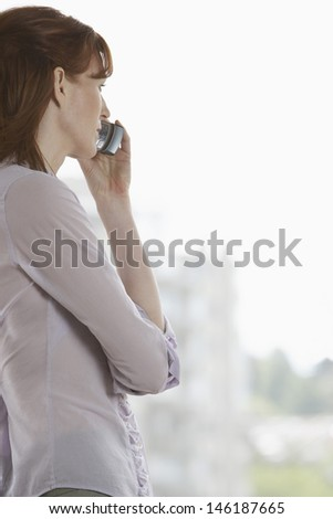 Side view of a businesswoman using mobile phone by window - stock photo
