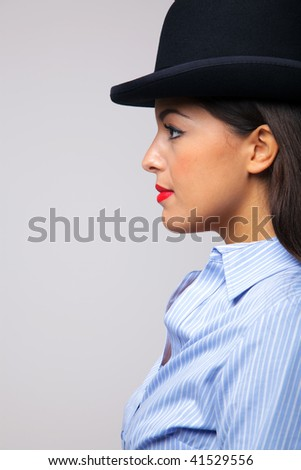 Side view of a businesswoman wearing a bowler hat. - stock photo