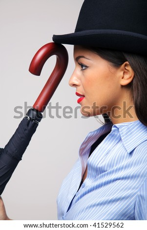 Side view of a businesswoman wearing a bowler hat and holding an umbrella. - stock photo