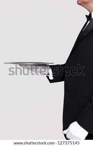 Side view of a butler holding a silver serving tray, blank background to add your own product. - stock photo