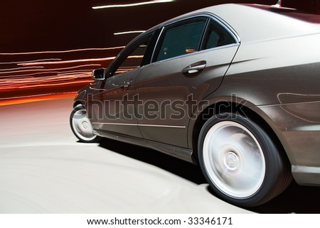 Side view of a car driving fast in the night - stock photo