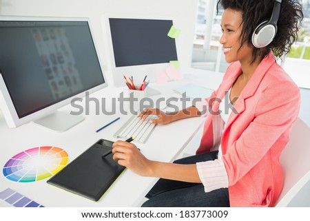 Side view of a casual female photo editor using computer in a bright office - stock photo