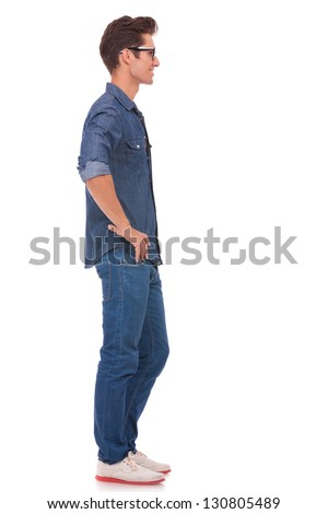 side view of a casual young man standing with his hands on his hips and looking away from the camera. isolated on a white background - stock photo