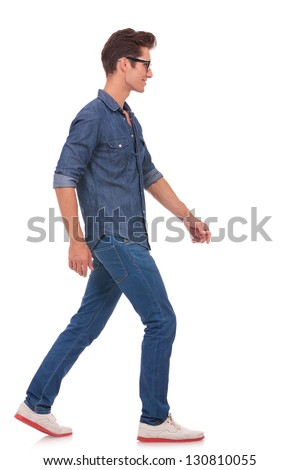 side view of a casual young man walking and looking forward, away from the camera. isolated on a white background - stock photo