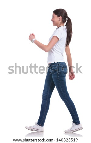 side view of a casual young woman walking and looking forward. isolated on white background
