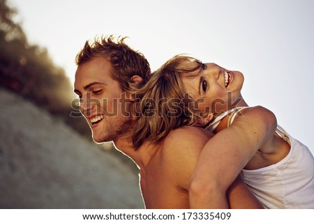 Side view of a cheerful young couple on the beach - stock photo