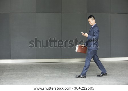 Side view of a Chinese businessman walking outdoors and using his Smart phone in modern Asian city. Business on the go concept. - stock photo