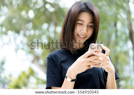 Side view of a college girl text messaging in the park