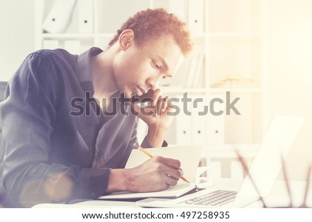 Side view of a concentrated african american businessman using notepad and laptop on office desktop while having mobile phone conversation.  Toned image