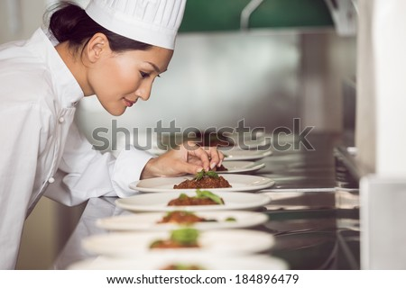 Side view of a concentrated female chef garnishing food in the kitchen - stock photo