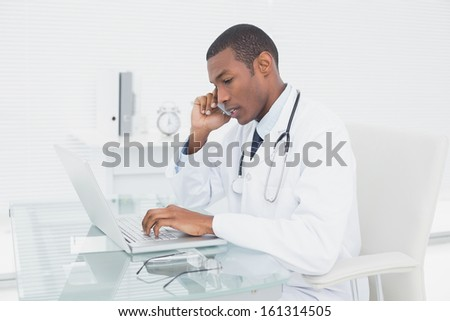 Side view of a concentrated male doctor using cellphone and laptop at medical office - stock photo