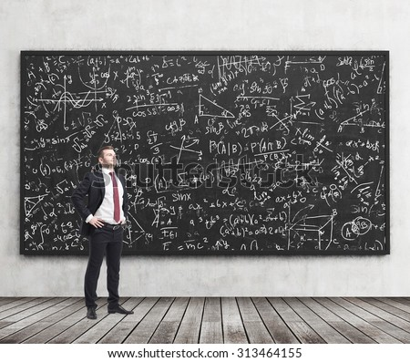 Side view of a confident young man who stands in front of black chalkboard which is full of math formulas. A concept of Analyst at investment bank. - stock photo