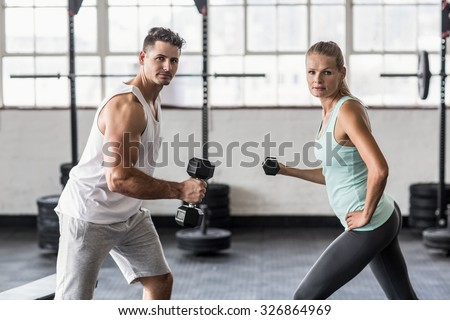 Side view of a couple exercising with dumbbells in gym - stock photo
