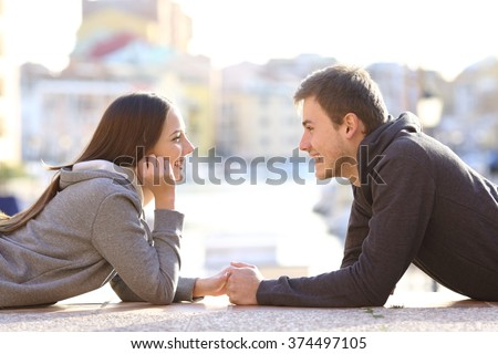 Side view of a couple of teenagers dating and flirting falling in love looking each other lying on the floor in a port on vacations - stock photo