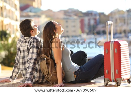 Side view of a couple of 2 tourists with a suitcase sitting relaxing and enjoying vacations in a colorful promenade. Tourism concept - stock photo