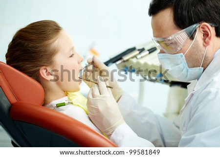 Side view of a dentist and his patient - stock photo