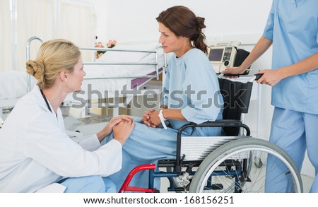 Side view of a doctor talking to a female patient in wheelchair at the hospital - stock photo