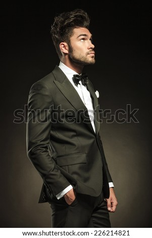 Side view of a elegant business man looking up while holding his right hand in pocket. - stock photo