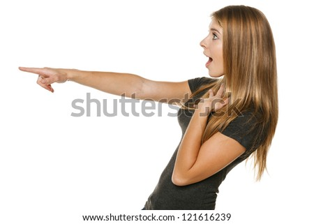 Side view of a excited casual female pointing out at copyspace, over white background - stock photo
