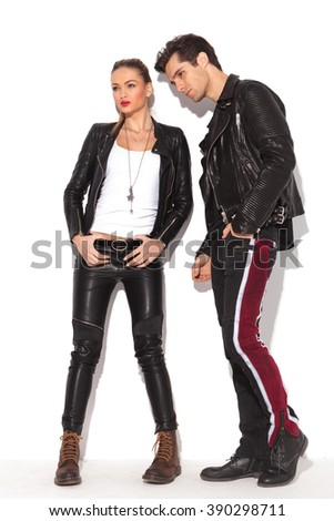 side view of a fashion couple in leather jackets standing in studio and look away from the camera - stock photo