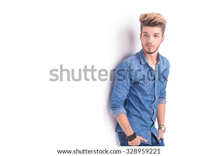 side view of a fashion man in jeans clothes looking away on white background - stock photo