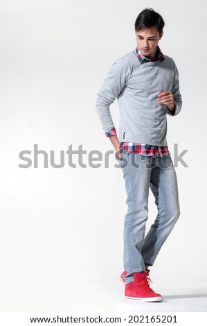 side view of a fashion man walking forward over in studio - stock photo