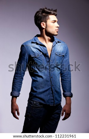 side view of a fashion young man looking to his left side on gray background - stock photo