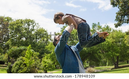 Side view of a father carrying son at the park - stock photo