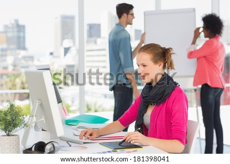 Side view of a female artist using graphic tablet with colleagues behind at the office - stock photo