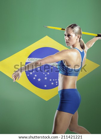 Side view of a female athlete preparing to throw javelin against white background - stock photo