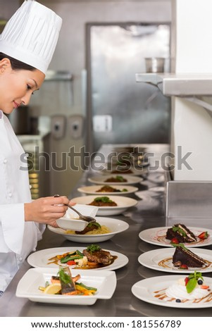 Side view of a female chef garnishing food in the kitchen - stock photo