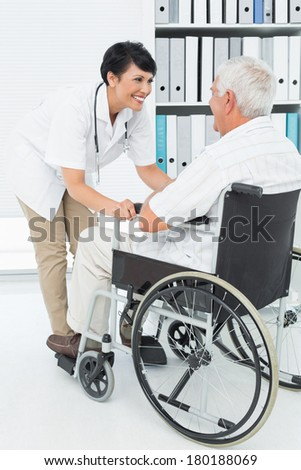 Side view of a female doctor talking to senior patient in wheelchair at the hospital