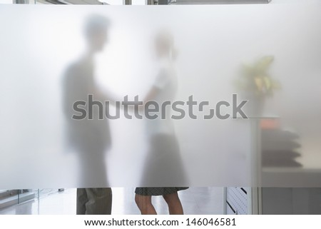 Side view of a female office worker touching male colleague behind translucent wall in office - stock photo