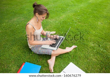 Side view of a female student using laptop with books at the park - stock photo