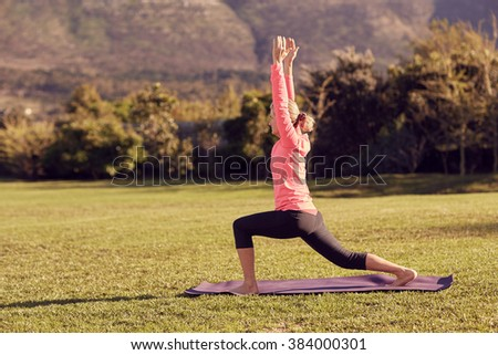 Side view of a fit and healthy senior woman in a deep warrior yoga pose, outdoors on a sunny morning, with her yoga mat laid out on the grass - stock photo