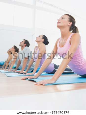 Side view of a fit class exercising in row at fitness studio - stock photo