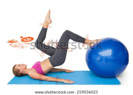 Side view of a fit woman exercising with fitness ball against fitness interface - stock photo