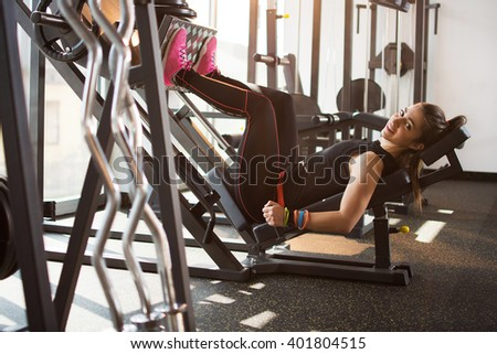 Side view of a fit young woman doing leg presses in the gym. - stock photo