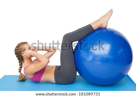 Side view of a fit young woman exercising with fitness ball over white background - stock photo