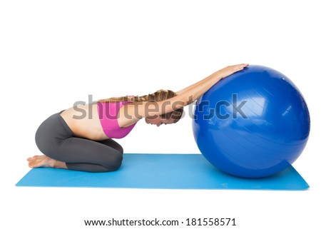 Side view of a fit young woman exercising with fitness ball over white background