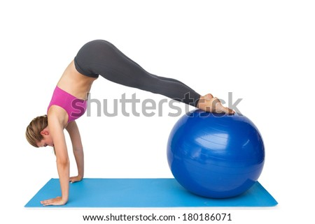 Side view of a fit young woman stretching on fitness ball over white background