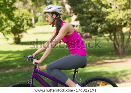 Side view of a fit young woman with helmet riding bicycle at the park - stock photo