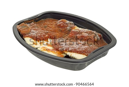 Side view of a frozen diet ravioli and sauce tv dinner on a white background.