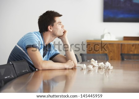 Side view of a frustrated young man sitting at conference table with crumpled papers - stock photo