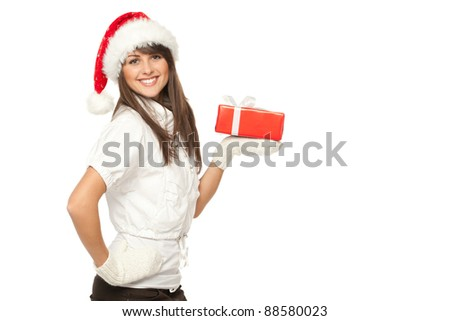 Side view of a girl in Santa hat holding a Xmas gift on her palm, isolated on white background - stock photo