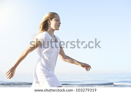 Side view of a girl walking along the shore on a beach with blue sky in the background. - stock photo